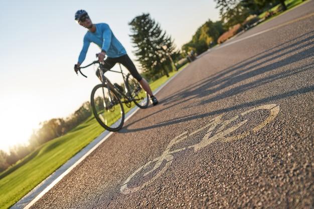 Ciclista professionista maschio in piedi con la sua bici su una pista ciclabile in background