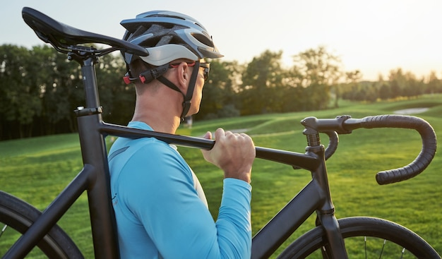 Ciclista professionista maschio che indossa abbigliamento sportivo e casco protettivo che guarda da parte mentre trasporta il suo