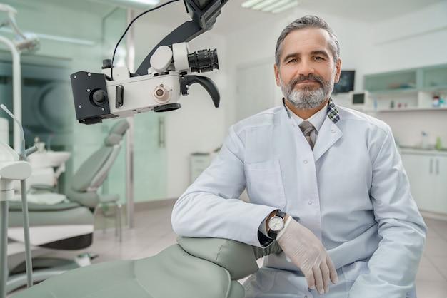 Dentista maschio professionista che esamina macchina fotografica e sorridere