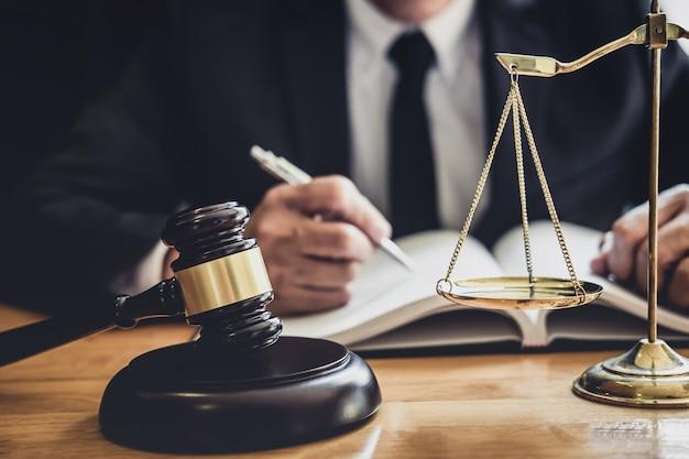 Avvocato o giudice maschio professionista che lavora con documenti contrattuali, documenti e martelletto e bilancia della giustizia sul tavolo in aula, concetto di legge e servizi legali