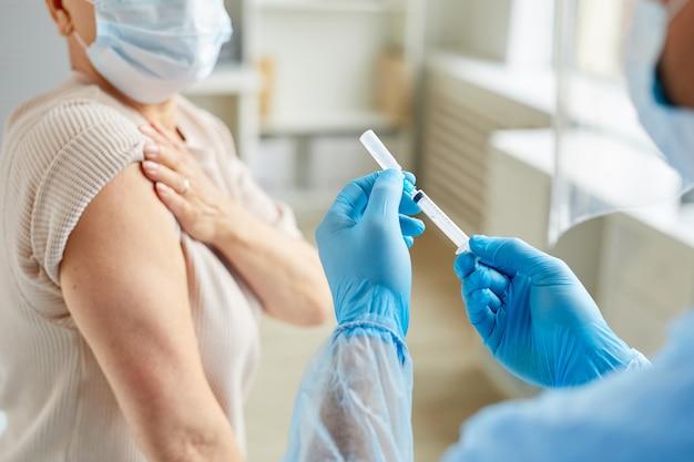 Infermiera maschio professionista che indossa maschera e guanti che preparano la siringa medica per l'iniezione al paziente