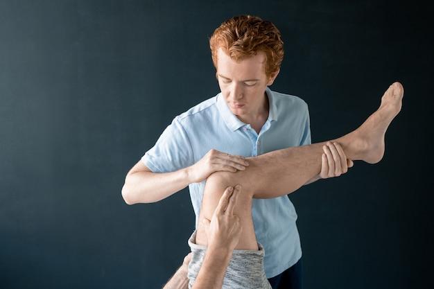 Medico professionista di riabilitazione maschile che tiene la gamba del paziente sdraiato sul lettino medico durante l'esercizio fisico e lo aiuta a piegarlo