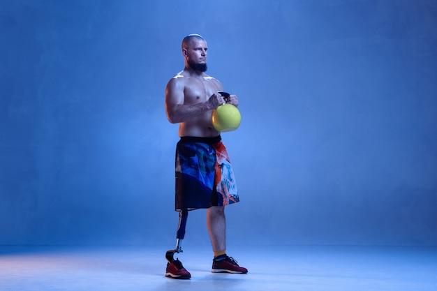 Sportivo professionista maschio con protesi alle gambe allenamento con kettlebell