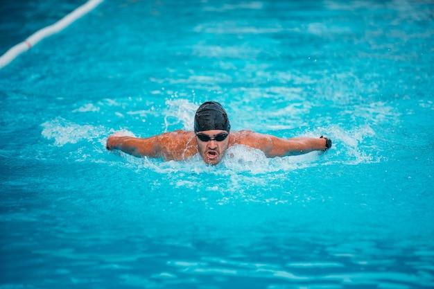 Uomo professionista che nuota in stile farfalla con cappello e occhiali in piscina