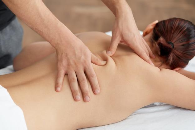 Massaggiatore professionista sta curando una paziente in appartamento.