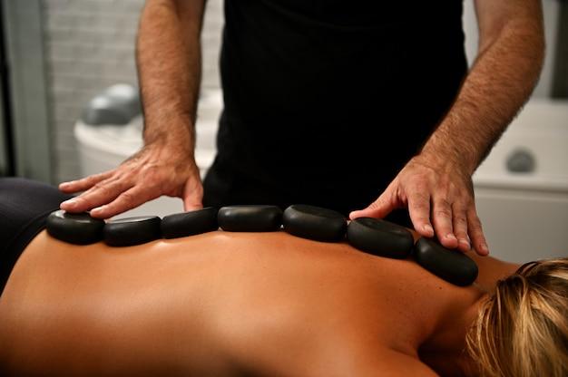 Massaggiatore professionista pone pietre calde lungo la spina dorsale della giovane donna e fa il massaggio ayurvedico con pietre calde nel moderno salone spa. schiena di donna con pietre nere allineate lungo la spina dorsale