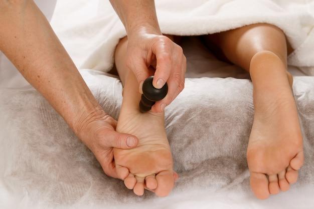 Massoterapia professionale - massaggio dei piedi con strumenti speciali
