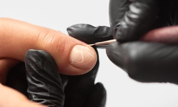 Manicure maestro professionista che lavora sulle unghie del cliente