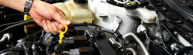 Un meccanico professionista tiene l'asta di livello dell'olio controlla il livello dell'olio nel lato del banner del motore dell'auto