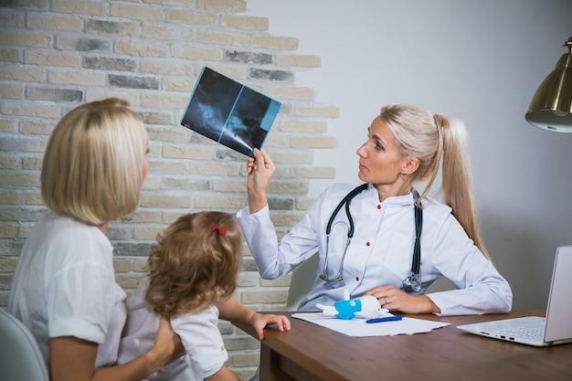 Il medico pediatra medico professionista in uniforme bianca consulta la madre con sua figlia. immagine dei raggi x dell'esame del pediatra del paziente del bambino