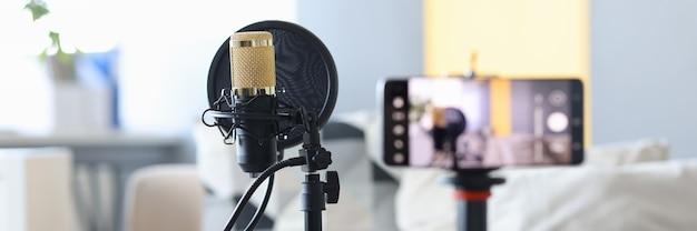 Microfono professionale in piedi vicino al concetto di studio di registrazione video domestico del primo piano della videocamera