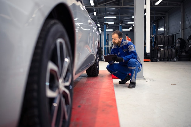 Meccanico di automobile caucasico barbuto di mezza età professionista che fa ispezione visiva del veicolo in officina e che tiene lista di controllo.