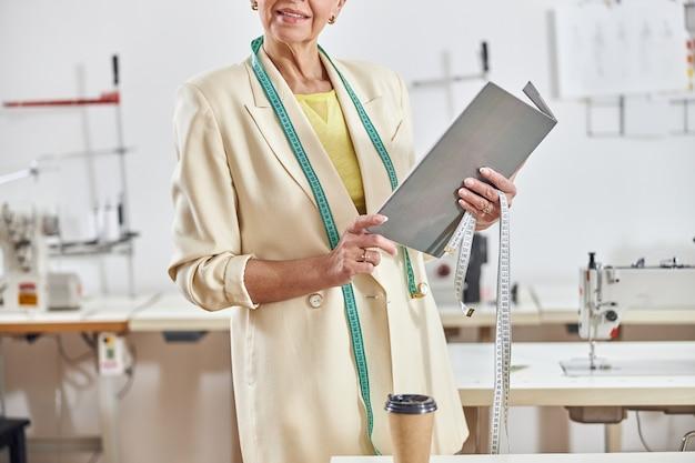 Sarta da donna professionale di mezza età con nastro verde in primo piano leggero del laboratorio di cucito