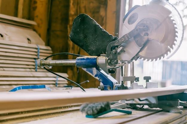 Troncatrice professionale in piedi su una pila di tavole con assi di rivestimento per il rivestimento della casa, la costruzione e il concetto di riparazione