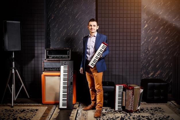 Musicista professionista con sintetizzatore tastiera da studio, fisarmonica e armonica