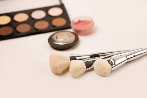 Pennelli naturali professionali e kit di modellamento in polvere su sfondo grigio