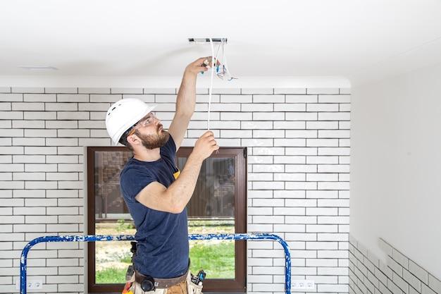 Professionista in tuta con strumenti sullo sfondo del sito di riparazione. concetto di ristrutturazione della casa.