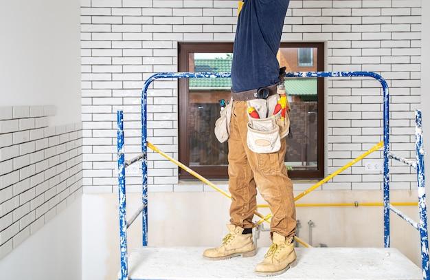 Professionista in tuta con strumenti sullo sfondo del sito di riparazione.