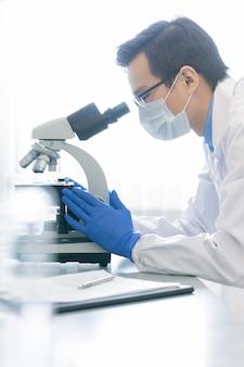 Farmacologo professionista utilizzando il microscopio