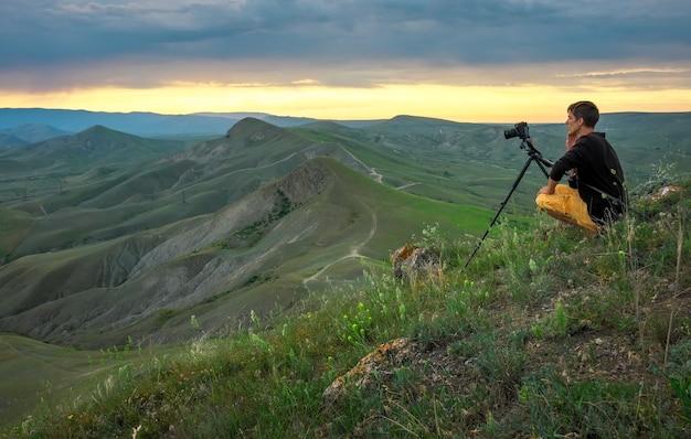 Fotografo professionista che utilizza un treppiede, scatta una foto di un paesaggio di montagna al tramonto
