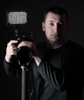 Fotografo professionista con fotocamera su treppiede.isolato su nero.