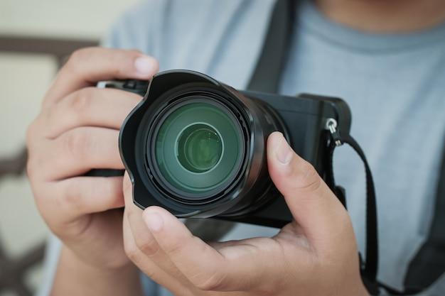 Fotografo professionista che lavora con la fotocamera mirrorless prima di scattare o scattare foto, messa a fuoco dell'obiettivo