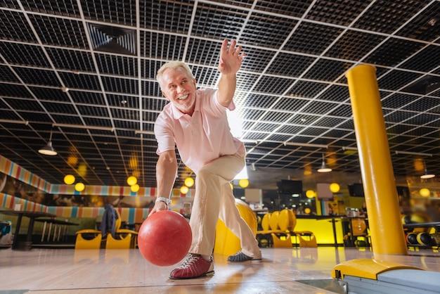 Giocatore professionista. uomo bello allegro che lancia la palla mentre gioca a bowling