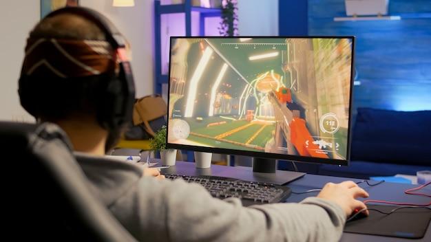 Giocatore professionista con cuffie che esegue videogioco sparatutto in prima persona con grafica moderna al campionato virtuale. streaming online cyber utilizzando la tecnologia di rete wireless