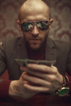 Giocatore di poker professionista in occhiali da sole che giocano nel casinò. giochi di dipendenza dal caso. uomo con le carte in mano svaghi nella casa da gioco