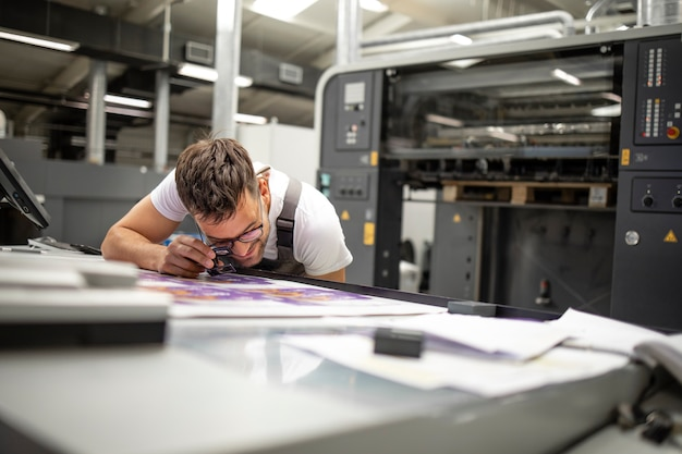 Addetto alla stampa professionista che controlla la qualità della stampa e la corrispondenza dei colori nella tipografia