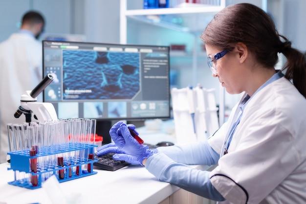 Scienziato professionista che esamina l'analisi della provetta del sangue per l'esperimento medico