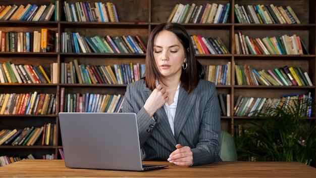 Segretaria professionista in costumi grigi su laptop seduto sotto un forte vento di ventola contro diversi libri colorati su scaffali in ufficio