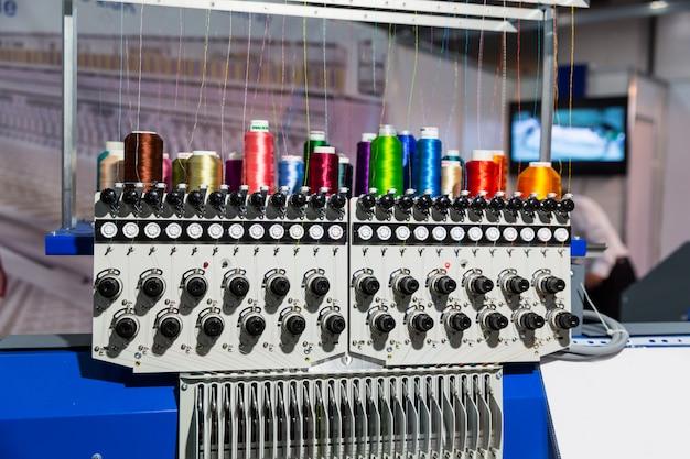 Macchina da cucire professionale con bobine di filo di primo piano. tessuto tessile, nessuno. produzione in fabbrica, produzione di cucito, tecnologia del ricamo