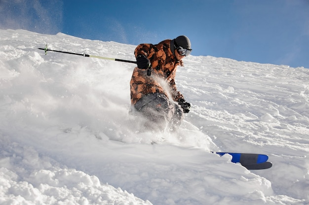 Uomo professionista dello sciatore che guida giù la pista da sci nella località turistica popolare di gudauri in georgia