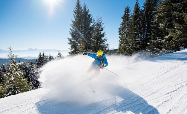 Sciatore professionista che scia in discesa in montagna. cielo blu e foresta invernale