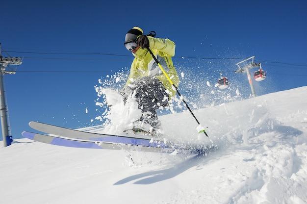 Sciatore professionista in abbigliamento sportivo giallo a cavallo lungo il pendio in georgia, gudauri