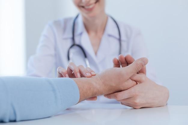 Professionista affascinante sorridente professionista che gode dell'appuntamento e prende il polso del paziente mentre applica le abilità professionali