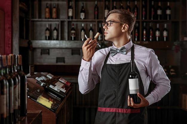 Sommelier professionista che sente l'odore di un tappo da una bottiglia di vino appena aperta