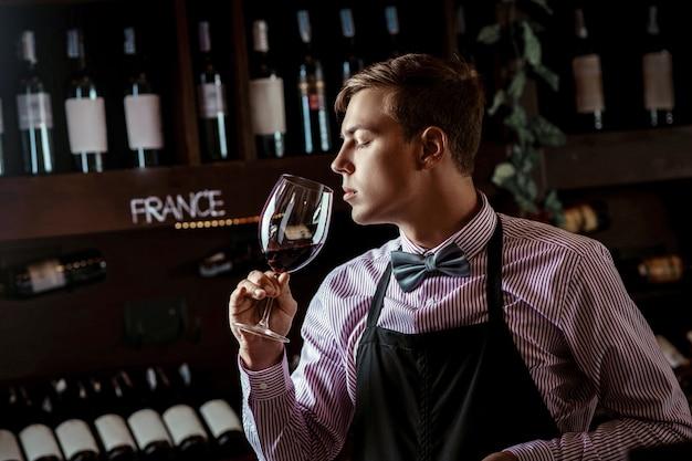 Sommelier professionista che annusa il vino rosso