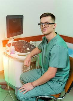 Ecografista professionista vicino alla moderna macchina ad ultrasuoni in clinica. diagnostica ad ultrasuoni