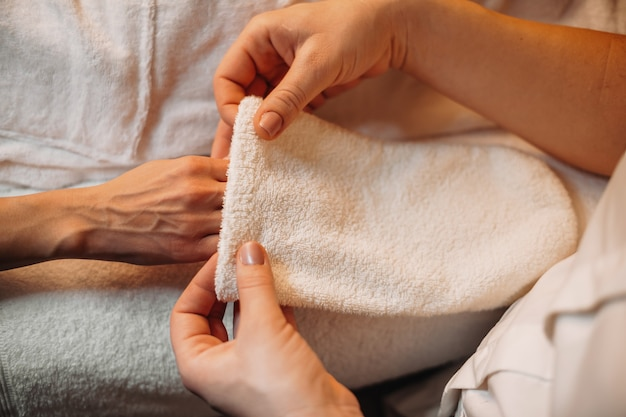 L'operatore spa professionista sta applicando un guanto speciale sulla mano del cliente prima di iniziare la procedura termale successiva