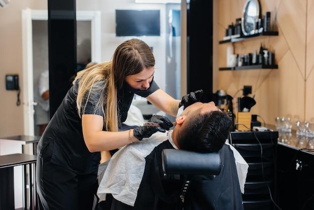 Uno stilista professionista in un barbiere moderno ed elegante rade e taglia i capelli di un giovane uomo. salone di bellezza, parrucchiere.
