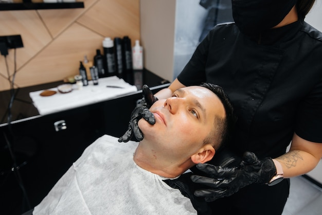 Uno stilista professionista in un barbiere moderno ed elegante rade e taglia i capelli di un giovane uomo.