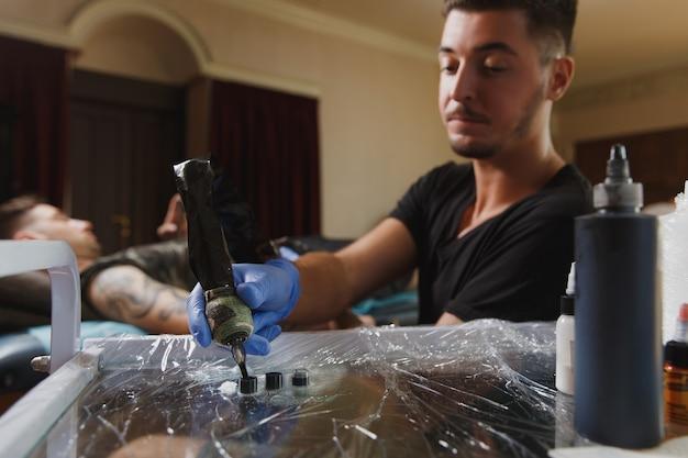 Un tatuatore professionista che fa un tatuaggio sul braccio di un giovane a macchina con inchiostro nero black