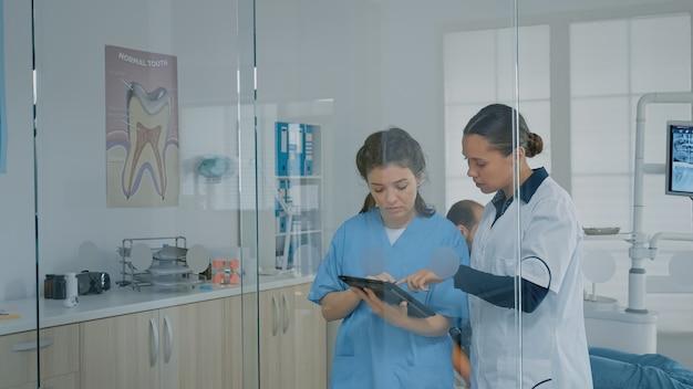Team professionale di stomatologi che guardano la tavoletta digitale