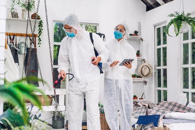 Team di professionisti per la disinfezione in maschera protettiva e virus per la pulizia dello spray disinfettante con tuta bianca
