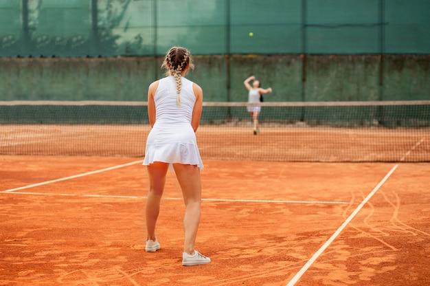 Giocatore di tennis professionista giocando a tennis su un campo da tennis in terra battuta in una giornata di sole.