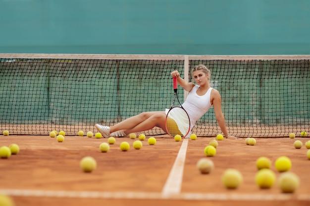Donna del giocatore di tennis professionista con racchetta e palla vicino a rete sul campo.