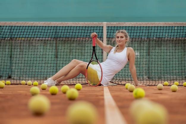 Donna del giocatore di tennis professionista con la racchetta e la palla vicino alla rete sul campo.
