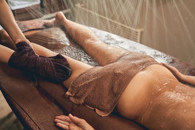 Terapista professionista che fa un massaggio rilassante alle gambe di riflessologia con asciugamani a una donna in spa